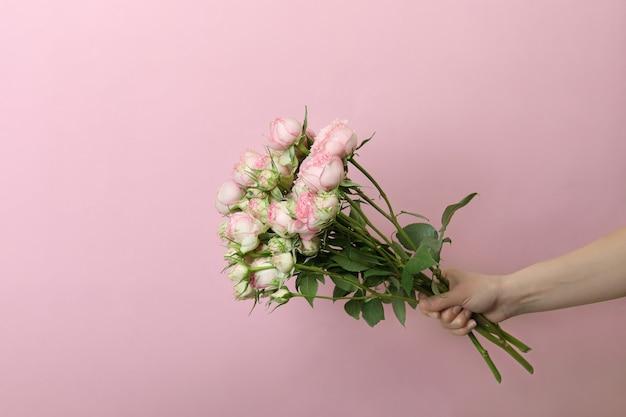 Mão feminina segurando rosas em rosa