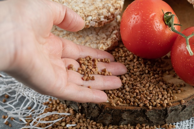 Mão feminina segurando trigo sarraceno cru de uma peça de madeira