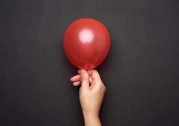 Mão feminina segurando um balão de ar vermelho inflado no preto
