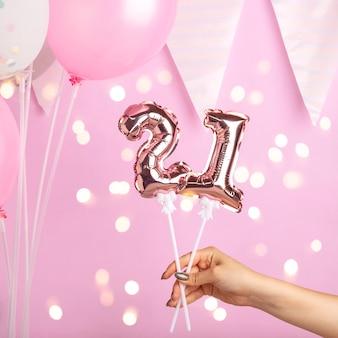 Mão feminina segurando um balão dourado em forma de número 21