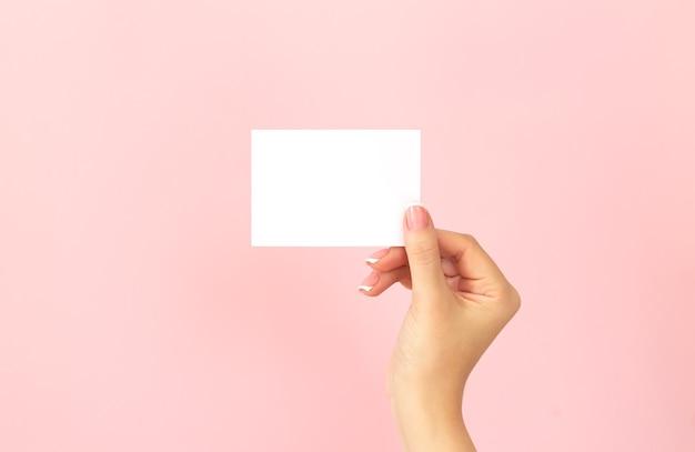 Mão feminina segurando um cartão de visita branco em branco, desconto ou folheto sobre fundo rosa