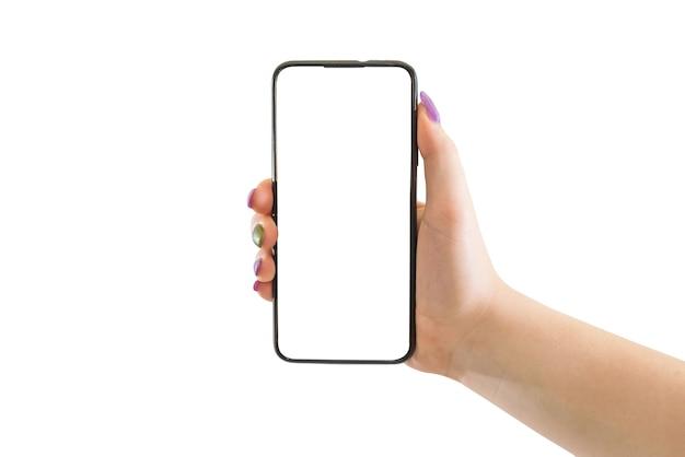 Mão feminina segurando um celular preto com uma tela branca em um fundo isolado.