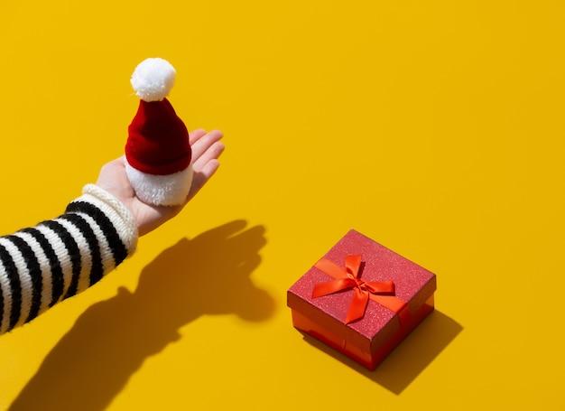Mão feminina segurando um chapéu de papai noel perto de uma caixa de presente na superfície amarela