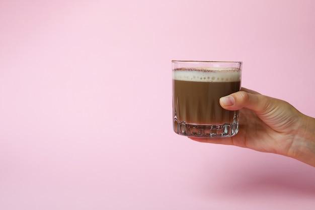Mão feminina segurando um copo de café irlandês no fundo rosa