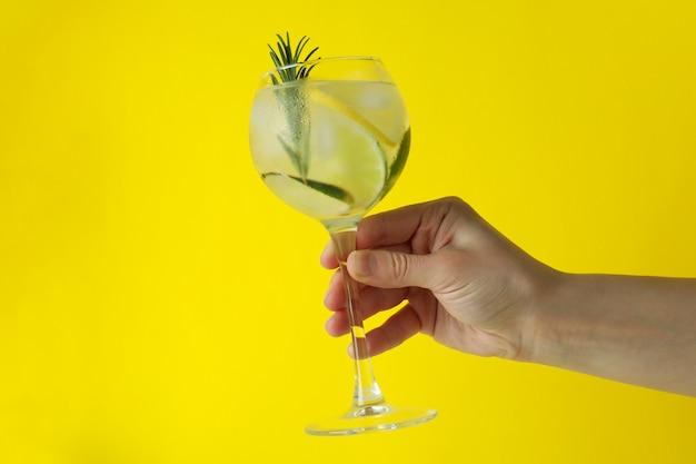 Mão feminina segurando um copo de coquetel com frutas cítricas e alecrim em fundo amarelo