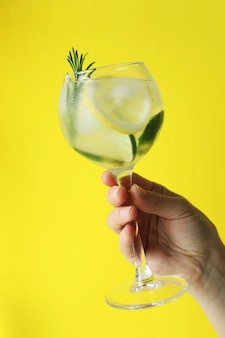 Mão feminina segurando um copo de coquetel com frutas cítricas e alecrim na superfície amarela