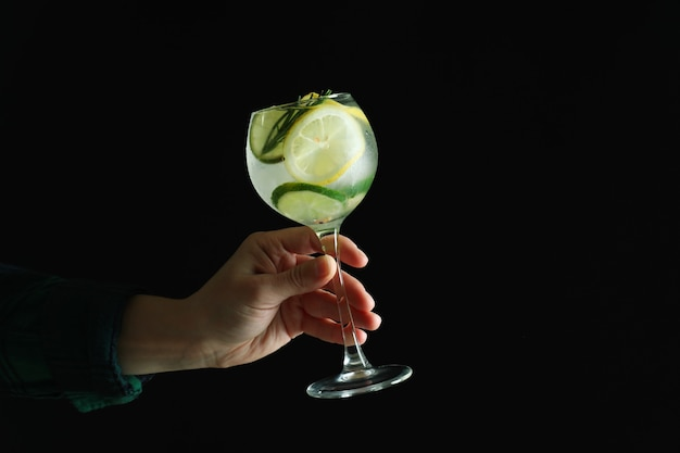 Mão feminina segurando um copo de coquetel com frutas cítricas na superfície escura