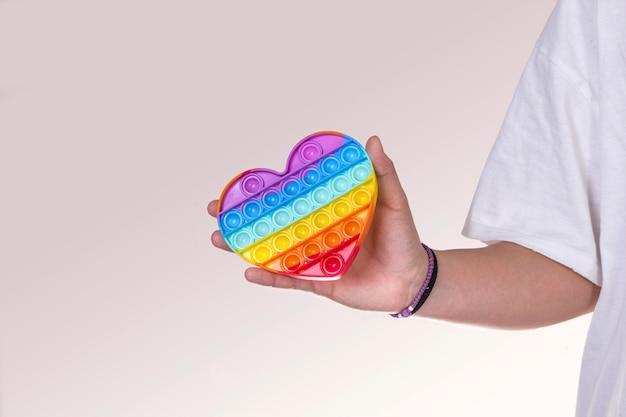 Mão feminina segurando um coração de arco-íris