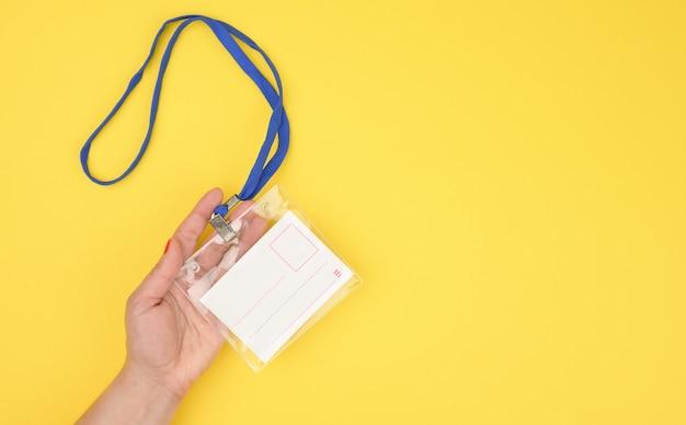 Mão feminina segurando um distintivo de plástico transparente em um cordão azul em um fundo amarelo