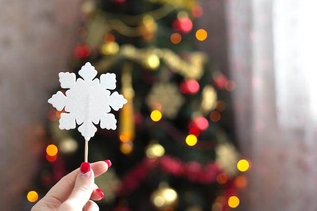 Mão feminina segurando um floco de neve de papel branco no fundo da árvore de natal com luzes