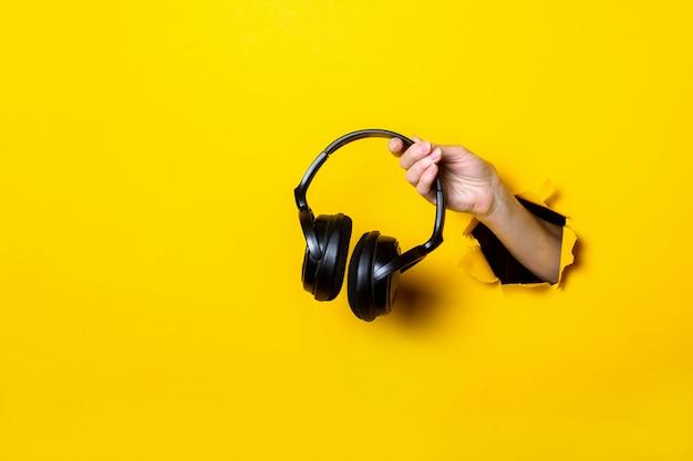 Mão feminina segurando um fone de ouvido preto em um fundo amarelo brilhante