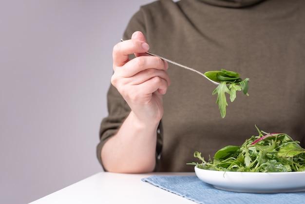 Mão feminina segurando um garfo com vegetais folhosos, um prato de folhas verdes em uma mesa de madeira