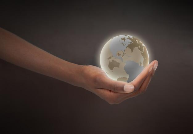 Mão feminina segurando um globo planetário brilhante