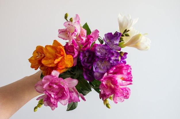 Mão feminina segurando um lindo buquê de flores coloridas