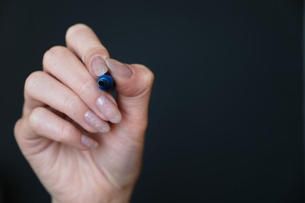 Mão feminina segurando um marcador de quadro branco azul em uma parede preta