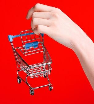 Mão feminina segurando um mini carrinho de compras sobre fundo vermelho. conceito de compras