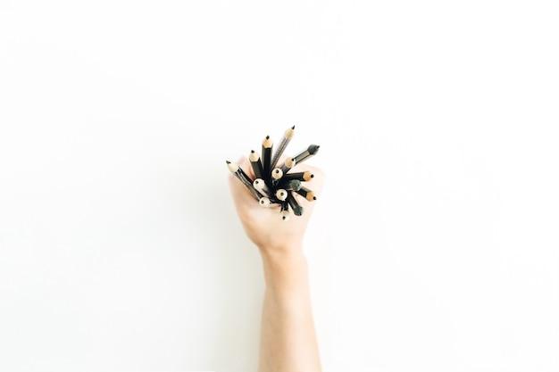 Mão feminina segurando um monte de lápis na superfície branca