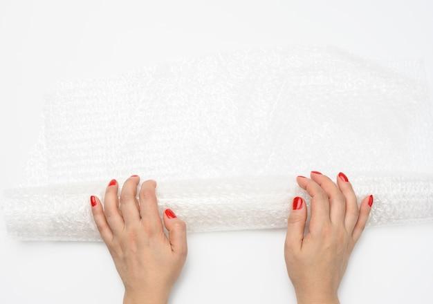 Mão feminina segurando um pedaço de polietileno amassado com bolhas de ar em um fundo branco, material de embalagem