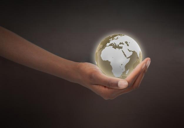 Mão feminina segurando um planeta globo