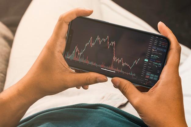 Mão feminina segurando um smartphone com gráfico do mercado financeiro de ações na tela. bolsa de valores. rio de janeiro, rj, brasil. setembro de 2021.