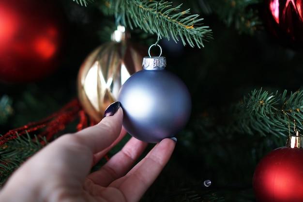Mão feminina segurando uma bola de natal azul no fundo de uma árvore de natal