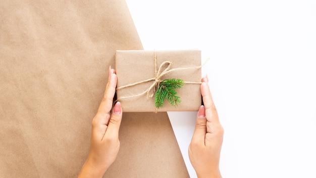Mão feminina segurando uma caixa de presente com um galho de árvore de natal
