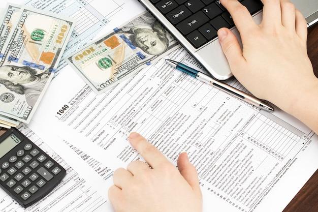 Mão feminina segurando uma caneta e usando a calculadora enquanto preenche a declaração de imposto de renda individual, close-up.