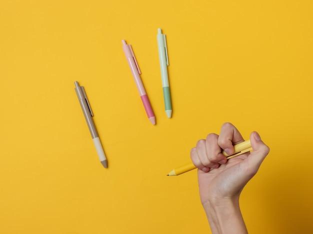 Mão feminina segurando uma caneta em um fundo amarelo