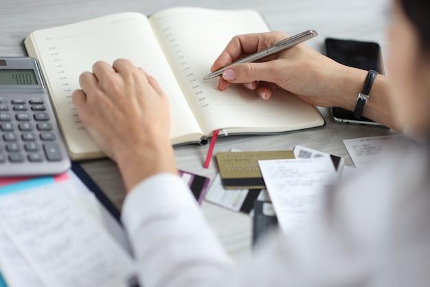 Mão feminina segurando uma caneta sobre o diário perto de cartões bancários e calculadora