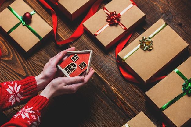Mão feminina segurando uma casa de brinquedo perto de caixas de presente