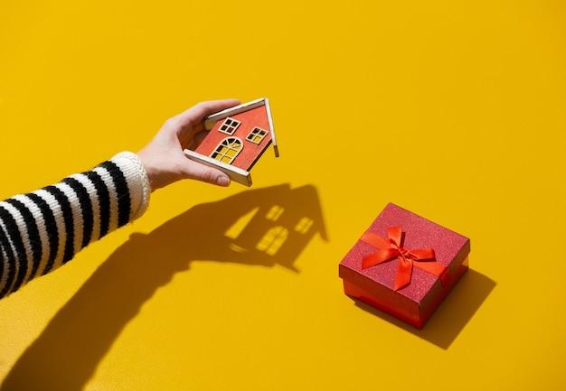 Mão feminina segurando uma casa de brinquedo perto de uma caixa de presente na superfície amarela