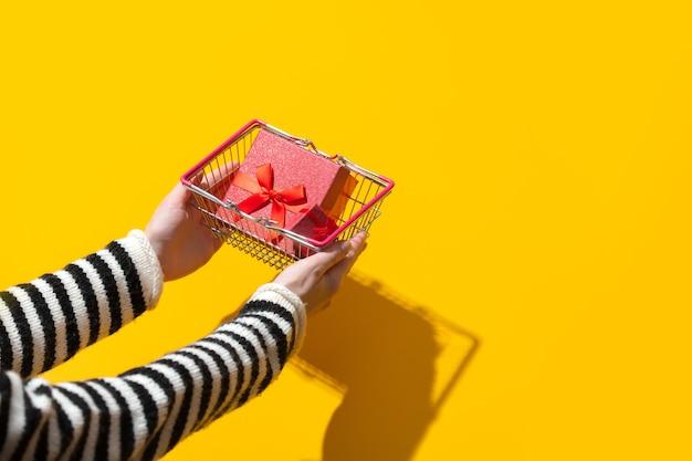 Mão feminina segurando uma cesta com caixa de presente na superfície amarela