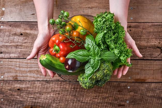 Mão feminina segurando uma cesta com legumes frescos e frutas no antigo fundo rústico de madeira, vista superior. espaço para texto. fundo de cozimento de alimentos e mock up.
