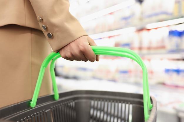Mão feminina segurando uma cesta de compras no fundo da loja
