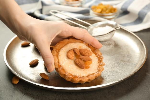 Mão feminina segurando uma deliciosa torta crocante com amêndoas e passas, closeup