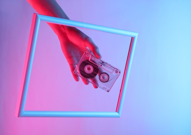 Mão feminina segurando uma fita cassete através de uma moldura elevada com luz de néon holográfica