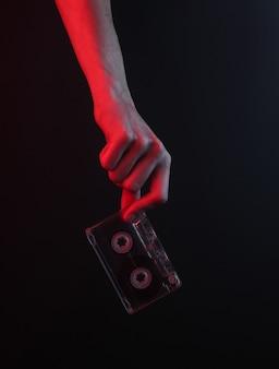 Mão feminina segurando uma fita cassete retrô em fundo preto com luz de néon vermelha