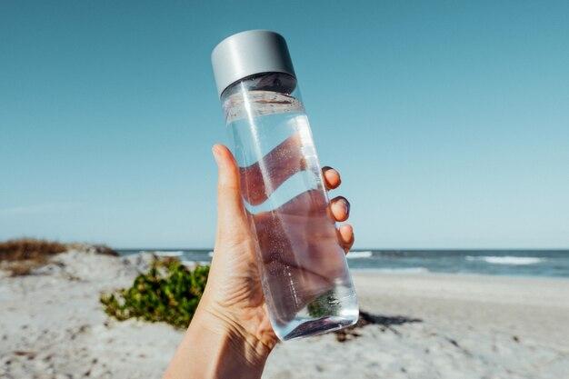 Mão feminina segurando uma garrafa de água potável ao ar livre na costa do mar conceito de cuidados de saúde fwater balance