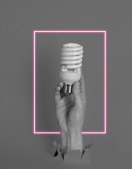 Mão feminina segurando uma lâmpada em espiral através de um papel rasgado com moldura de néon
