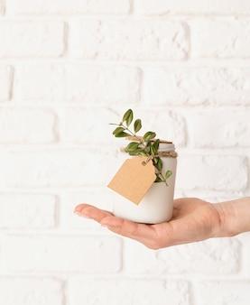 Mão feminina segurando uma linda vela branca com folhas frescas na superfície de tijolo branco