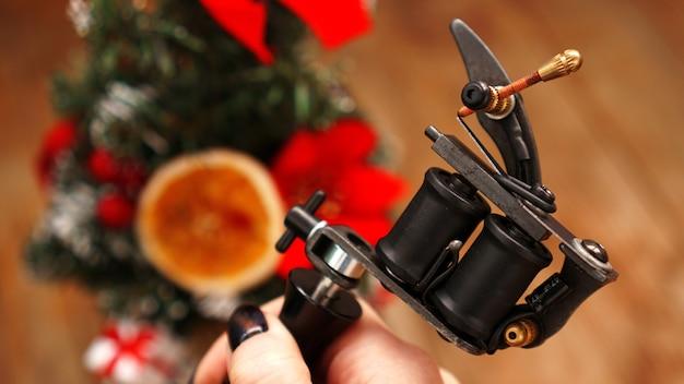 Mão feminina segurando uma máquina de tatuagem preta no fundo desfocado da árvore de natal