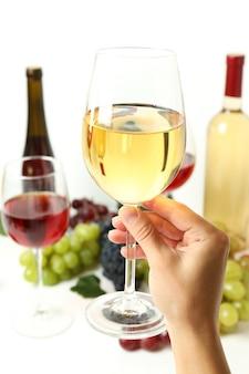 Mão feminina segurando uma taça de vinho branco contra vários vinhos
