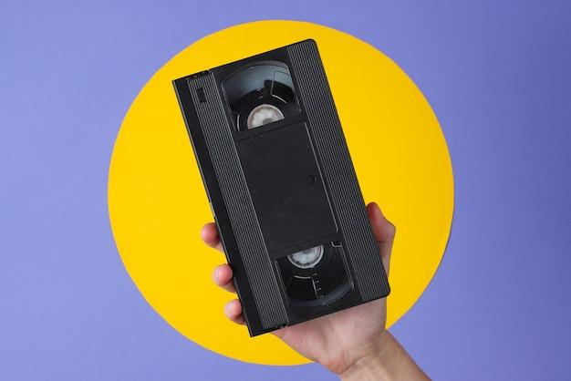 Mão feminina segurando videocassete em roxo com círculo amarelo