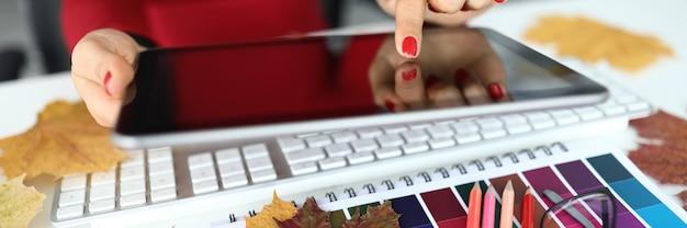 Mão feminina segurar o tablet pc contra closeup de mesa de escritório. conceito de educação profissional