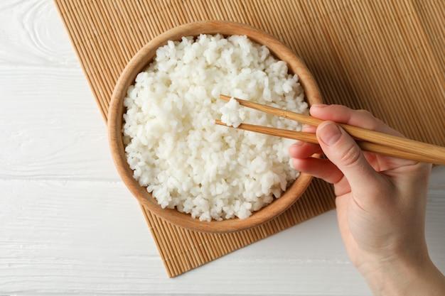 Mão feminina segurar os pauzinhos na superfície de madeira com arroz delicioso