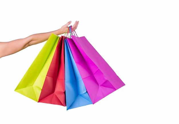 Mão feminina segurar sacos de papel de cor isolados