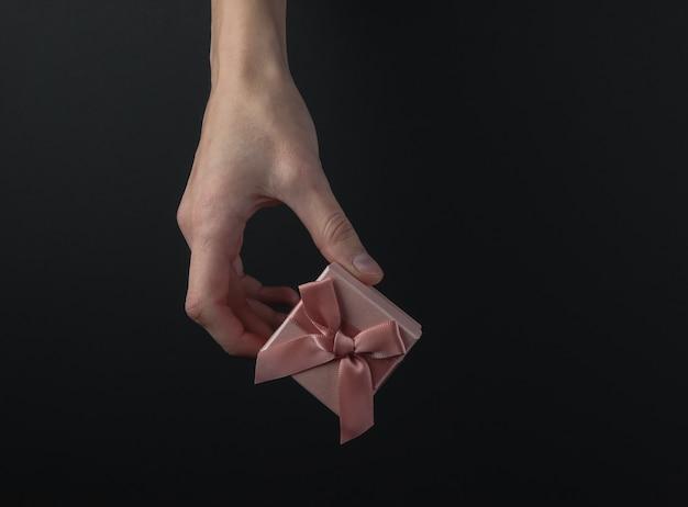 Mão feminina segure a caixa de presente com um laço em um fundo preto. conceito black friday