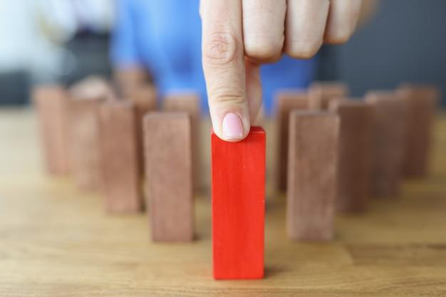 Mão feminina seleciona bloco de madeira vermelho entre os marrons.