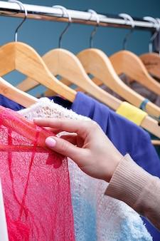 Mão feminina seleciona novas roupas coloridas em cabides de madeira na prateleira na loja, closeup. conceito de compras