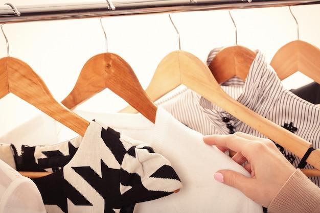 Mão feminina seleciona novas roupas da moda em cabides de madeira na prateleira em fundo branco, closeup. conceito de compras